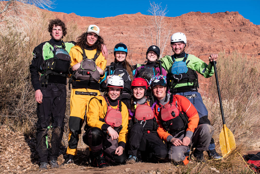 Group of paddlers posed for picture with canyon wall in background