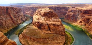 River wraps around a rock formation in the Grand Canyon