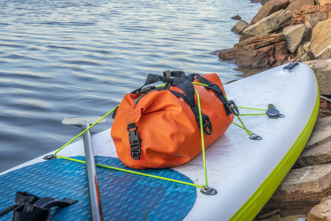 Inflatable paddleboard with bag strapped to front end