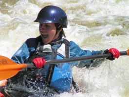 Woman holding into a kayak paddle, wearing red gloves