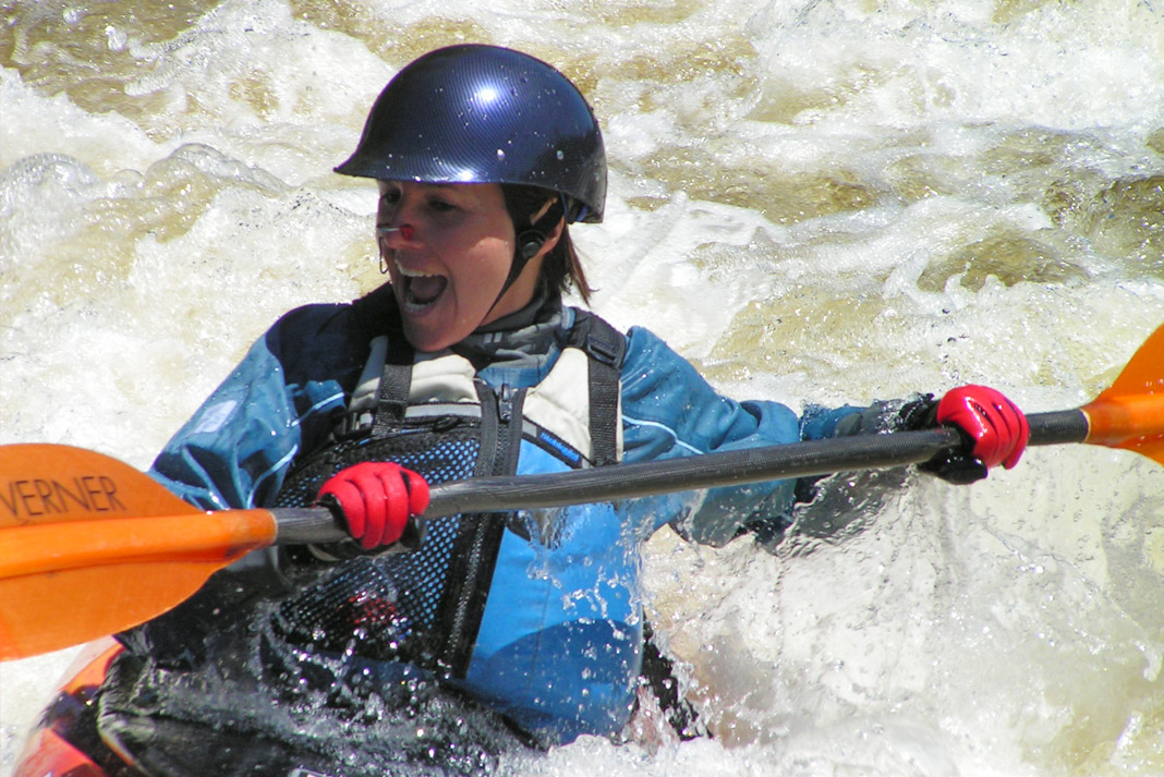 Woman holding a kayak paddle and wearing gloves