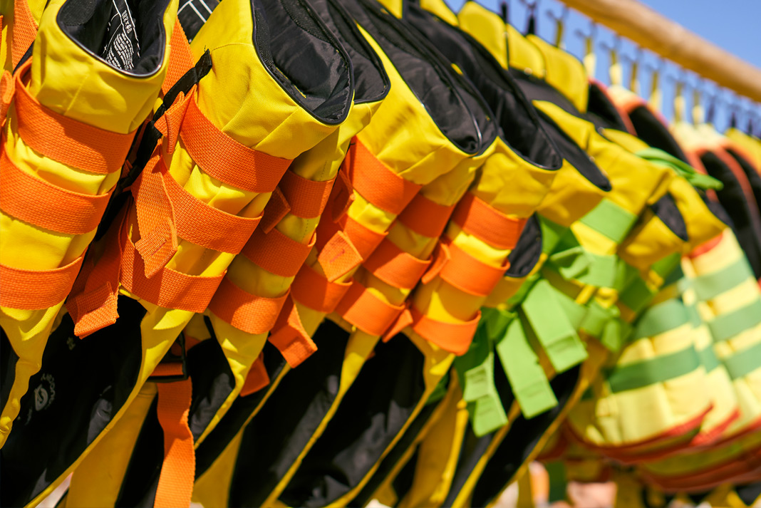 Row of life jackets hung up on a rack