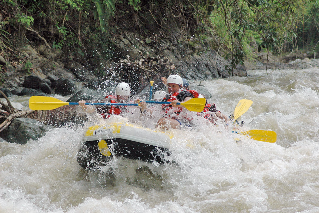 People being flooded by a wave in a raft