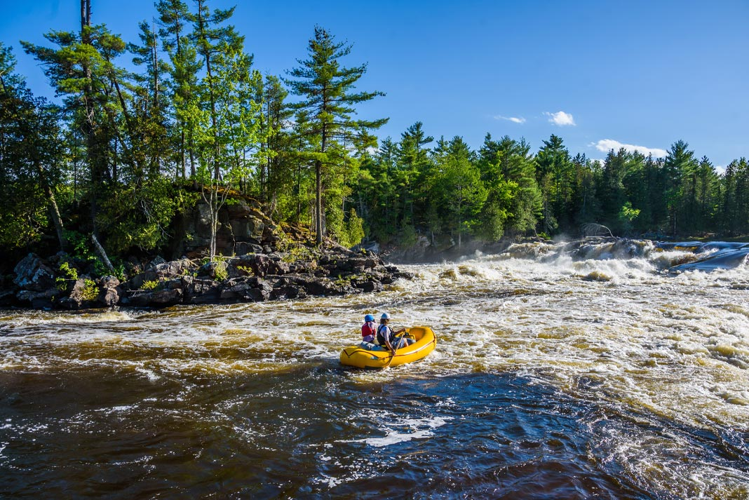 A father and son paddle a yellow raft down a river.