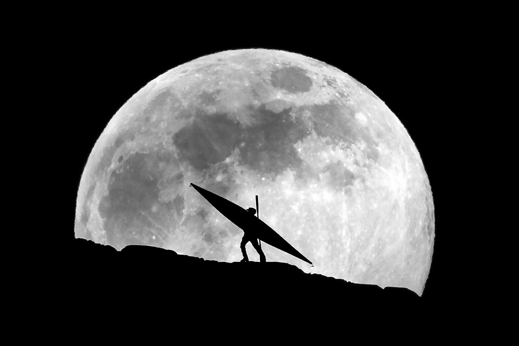 A kayaker silhouetted against the full moon