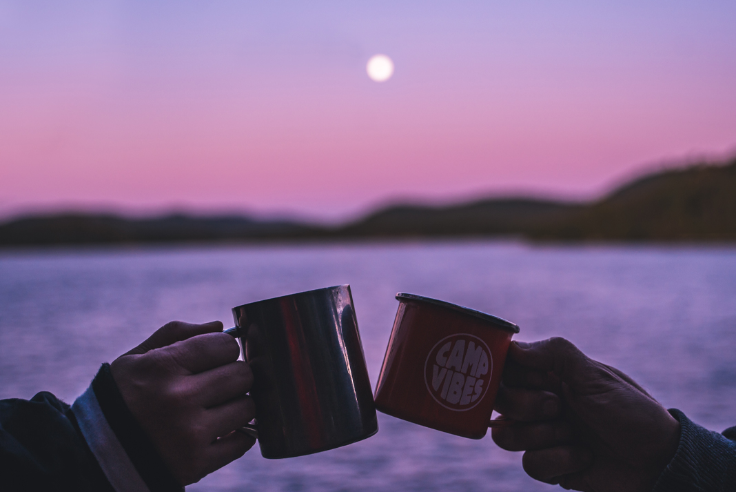 Two hands clink camping mugs in front of a lake during a pink and purple sunset