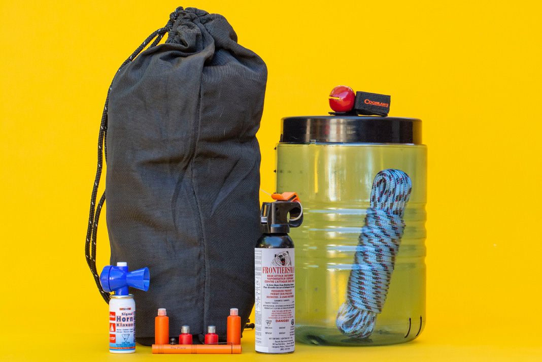 Camping gear for bear safety on a yellow background.