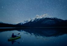 A paddler kayaks towards a mountain under a starry sky at night.