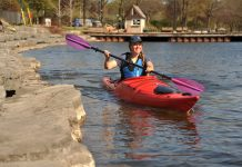 A woman kayaks along the shore in a red kayak with a purple paddle.