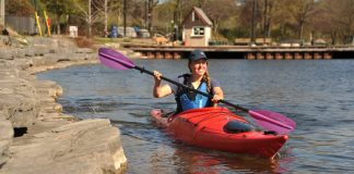 A woman paddles along the shore in a Pakayak Bluefin 14 packable kayak