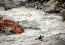 A woman paddles the amazon river in a red whitewater kayak