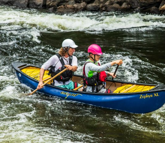 A father and son paddle a blue Esquif Zephyr 2.0 XL whitewater canoe.