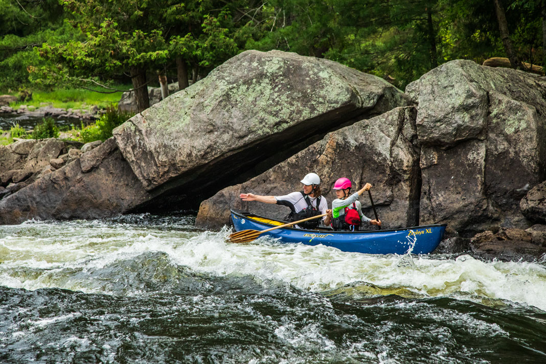 A father and son paddle a blue whitewater canoe.