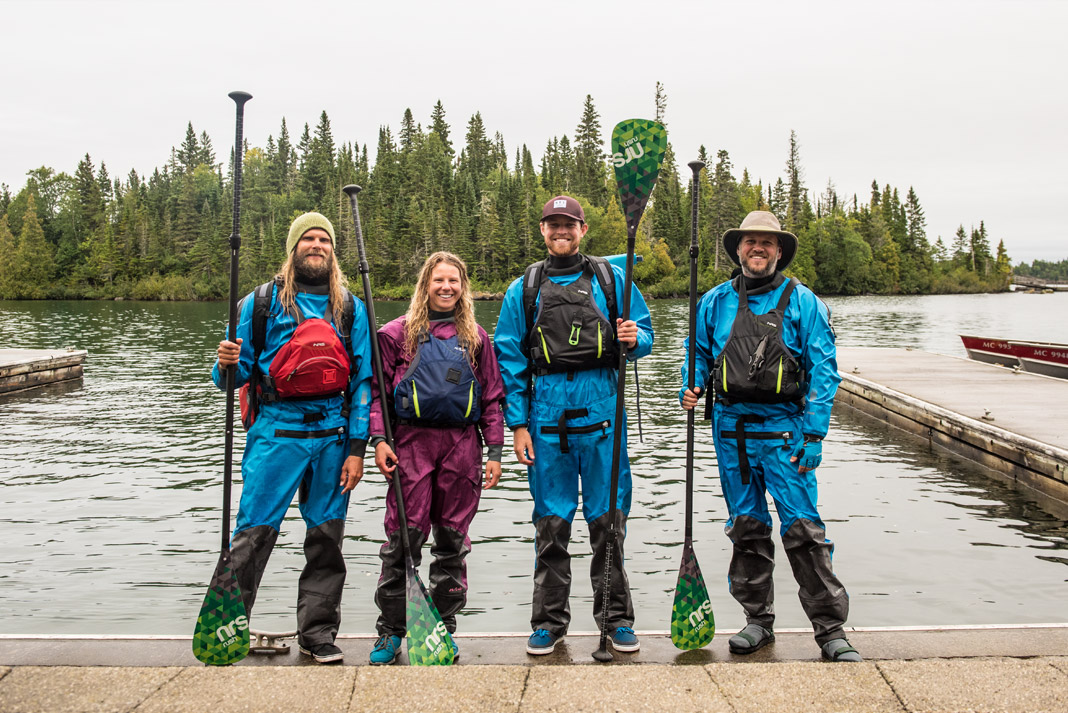 A group of paddleboarders pose in their gear and the boat launch.
