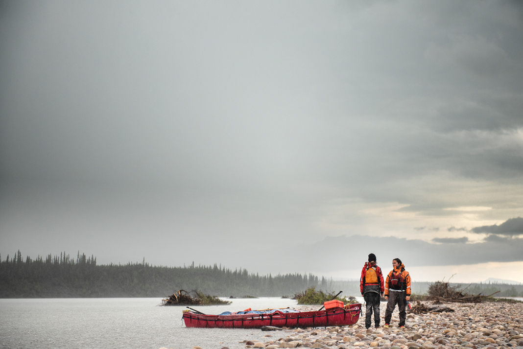 Two paddlers stand beside a lake with their canoe in the backcountry.