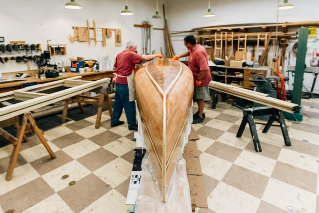 Two craftsmen repair a wooden canoe in a shop
