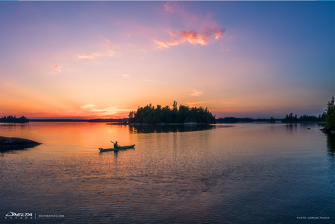 A kayaker paddles towards and island at sunset