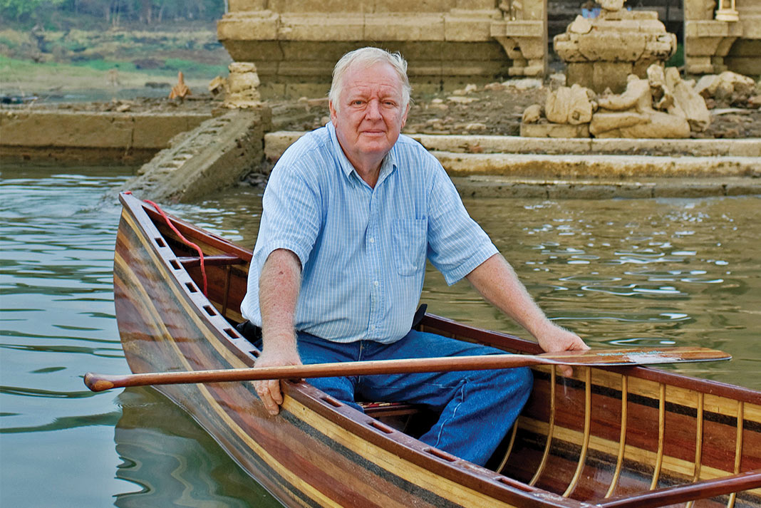Man sitting in a wooden canoe