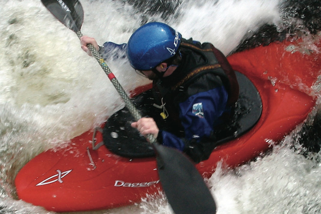 man paddles through whitewater rapids in a Dagger Juice kayak