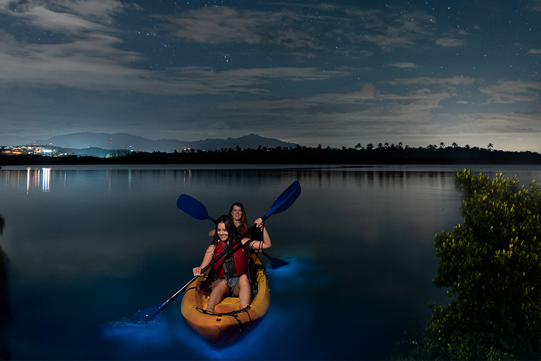 Girls kayaking on a bioluminescent bay under a cloudy night sky