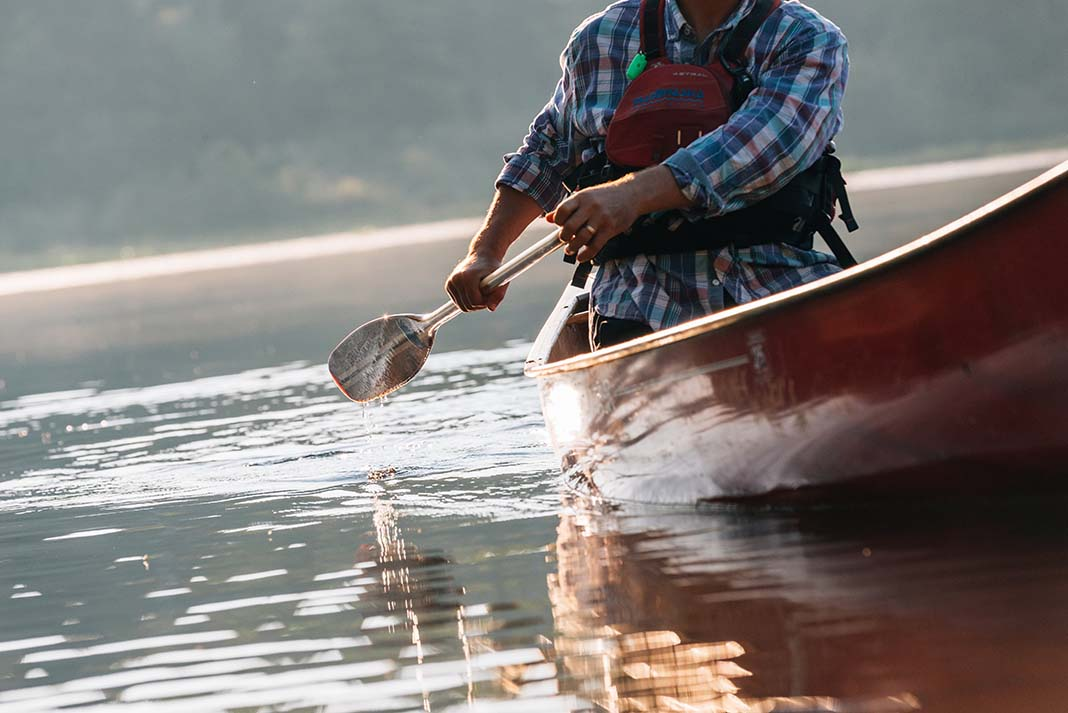 A paddler solo canoes across a lake in Algonquin Park