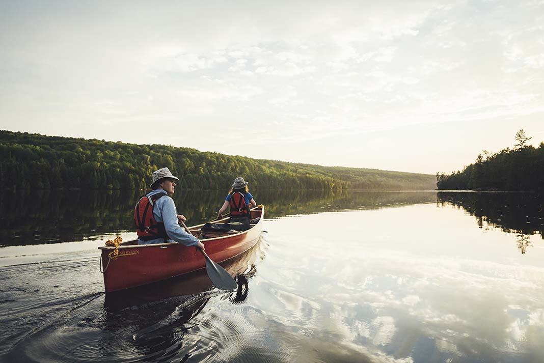 A couple paddles a red canoe across a lake in Algonquin Park