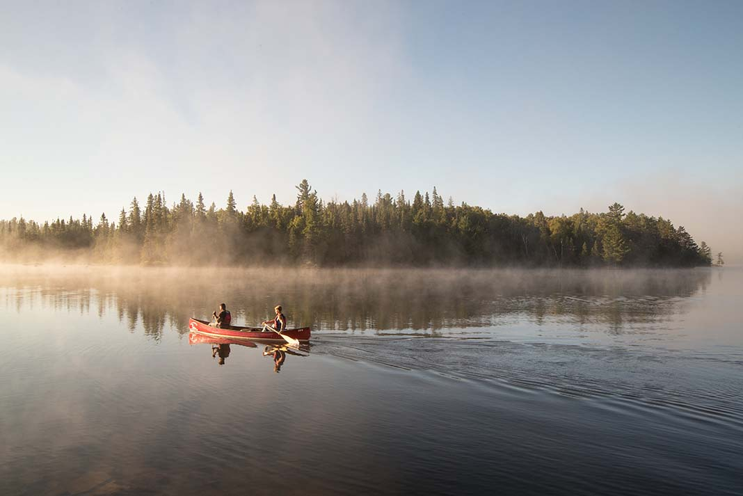 Canoeists paddle across a misty lake in the Algonquin Park backcountry
