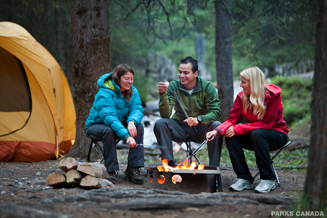 Three people enjoying the campfire in the woods