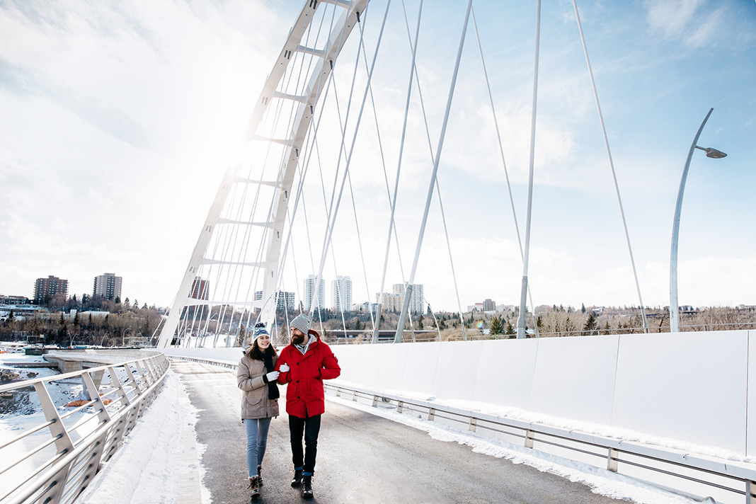 Two people standing on a bridge over a frozen river