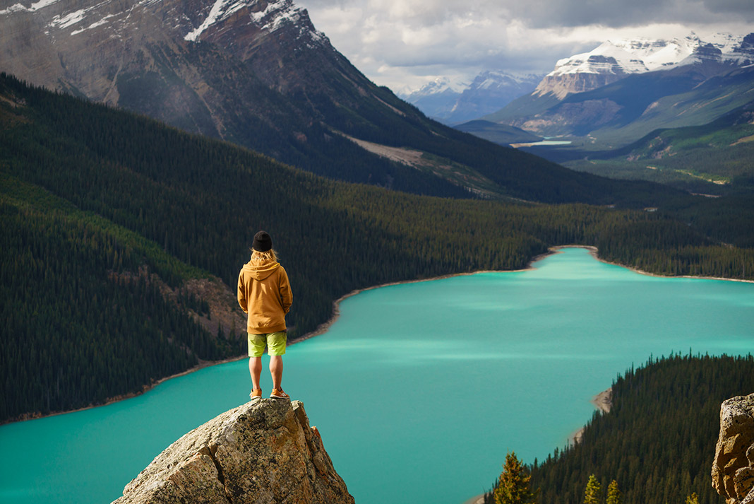 A person stands on a rock overlooking Moraine Lake