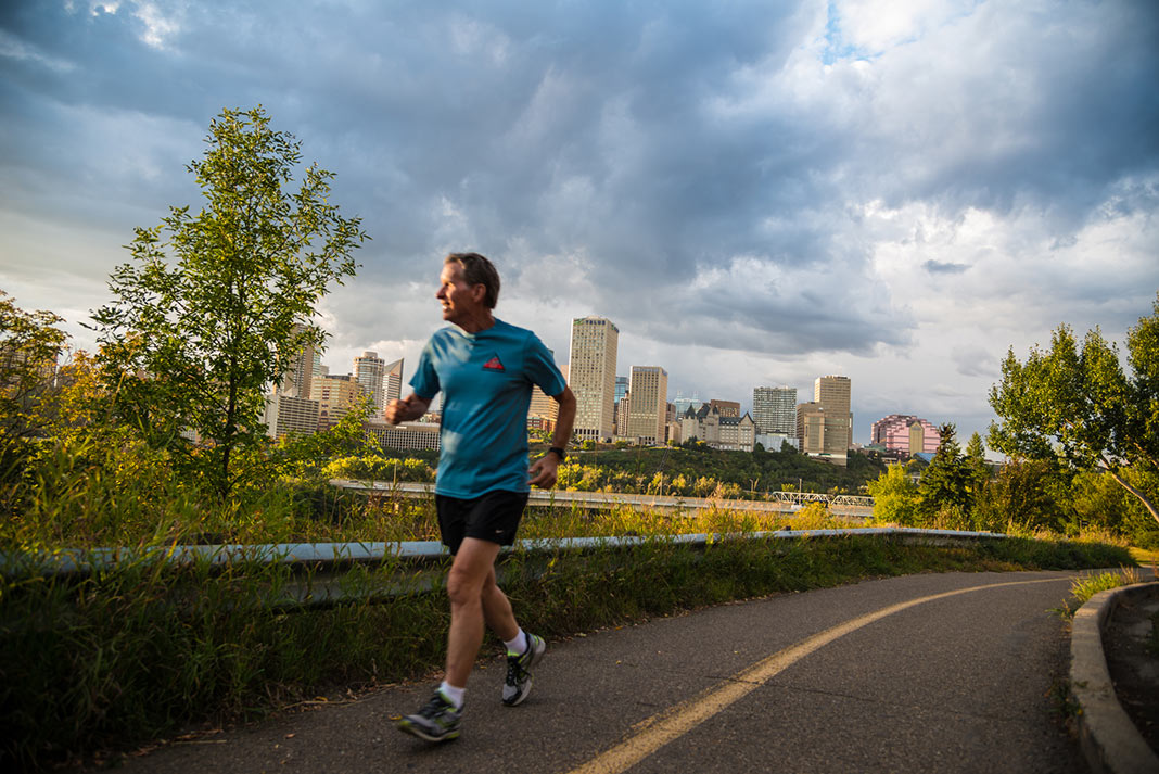 A jogger running with the city of Edmonton in the background