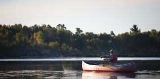 A angler fishes from a canoe in Algonquin Park