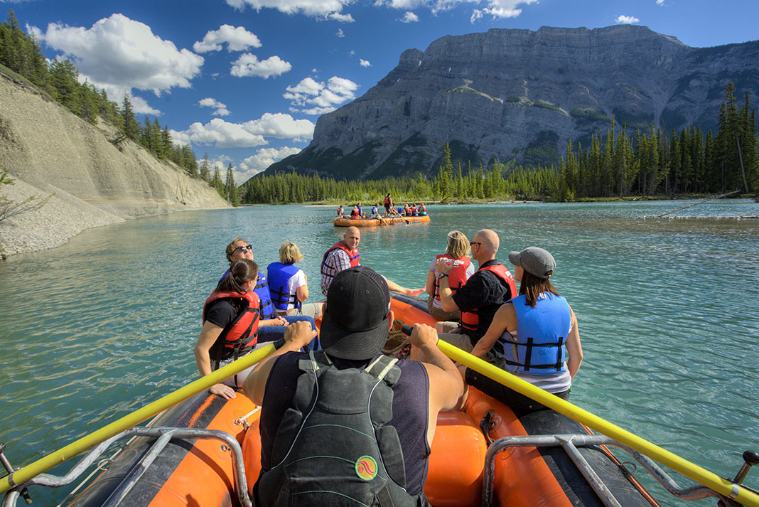 View from the back of a raft on the Bow River with mountain in background