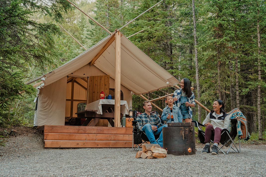 Group of people sitting in front of glamping tent