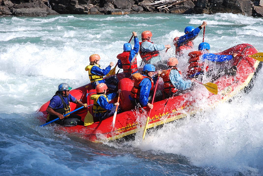 People hitting a big wave in a red raft