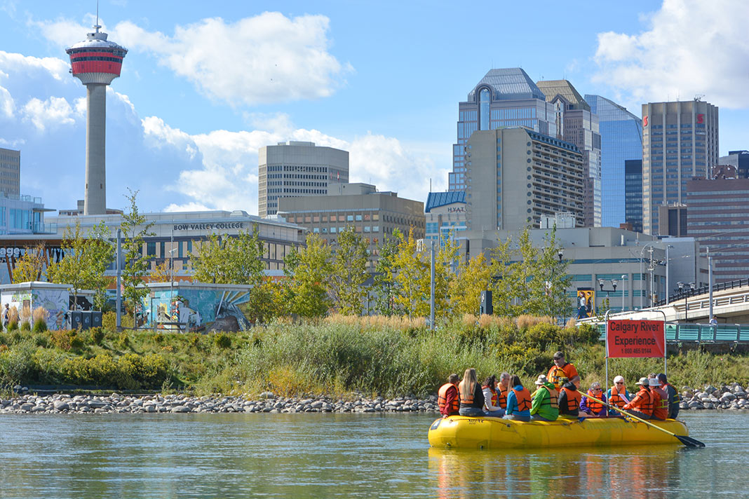 People in yellow raft on river with Calgary buildings in background.