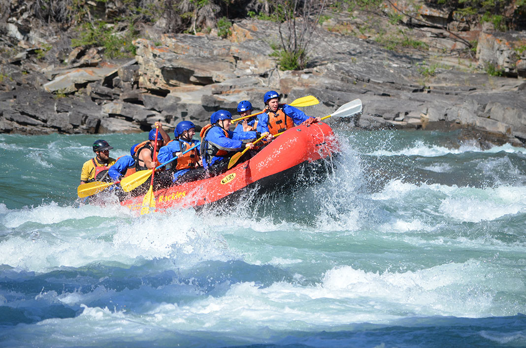 People whitewater rafting in a red raft on the Bow