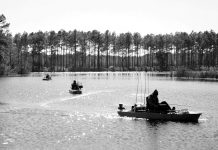 men kayak fishing on a lake surrounded by trees