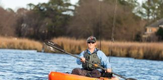 man paddling an orange native watercraft fishing kayak