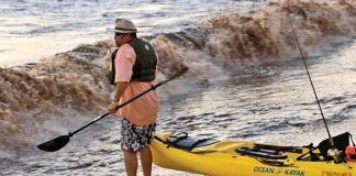 Kayak Angler Launching Kayak Into Ocean