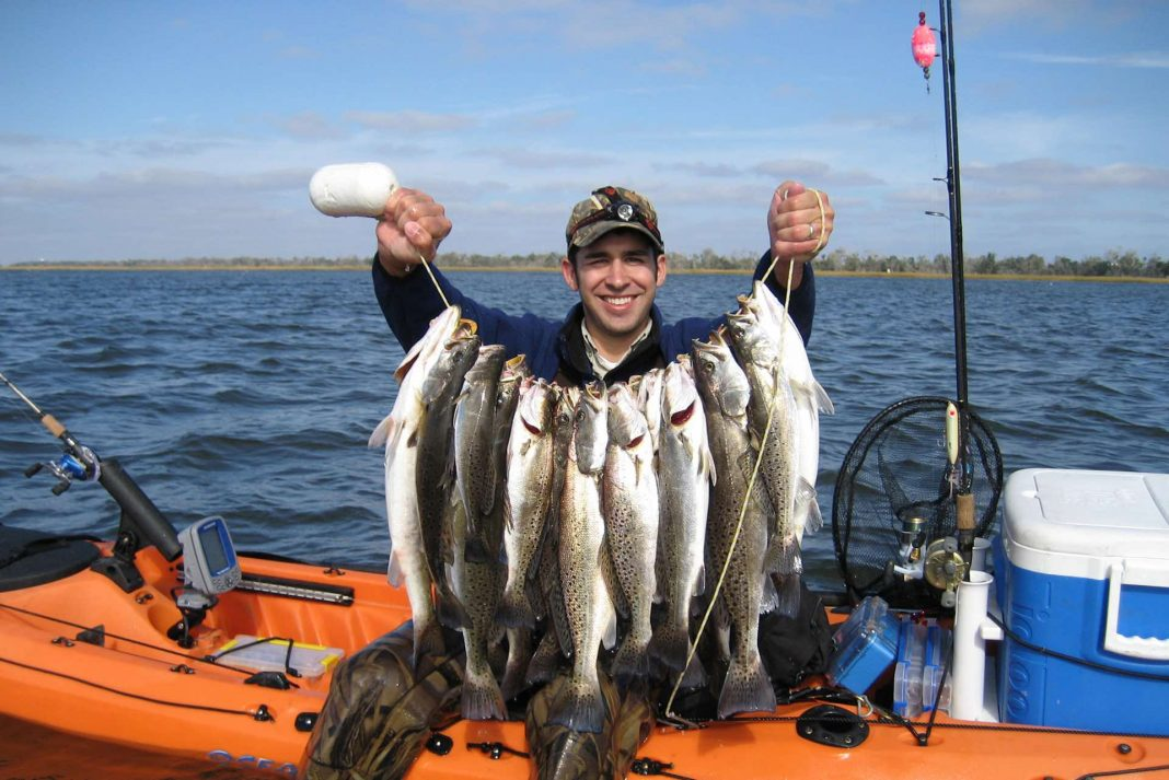 Angler holds up stringer of sea trout on kayak