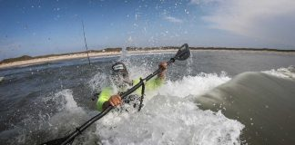 Angler rides the surf in a fishing kayak