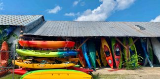 Kayaks stacked for sale in front of a building