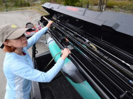 angler loading her rods into carrying rack
