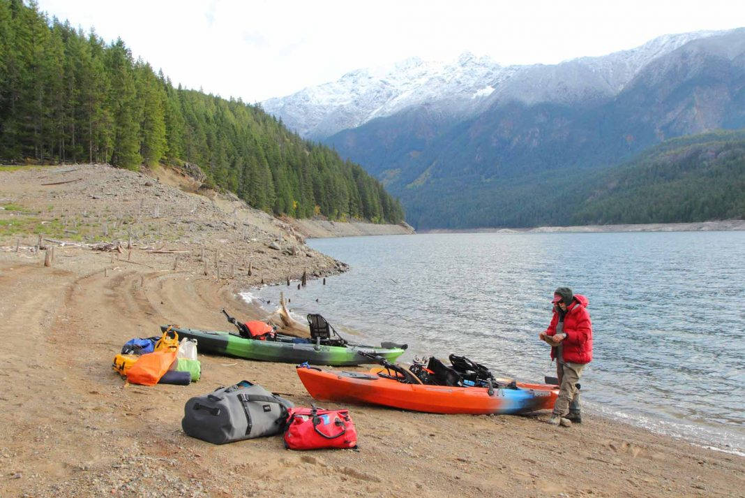 kayak anglers prepare on the shore of Ross Lake in Washington