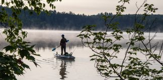 Person standing on kayak on a misty lake