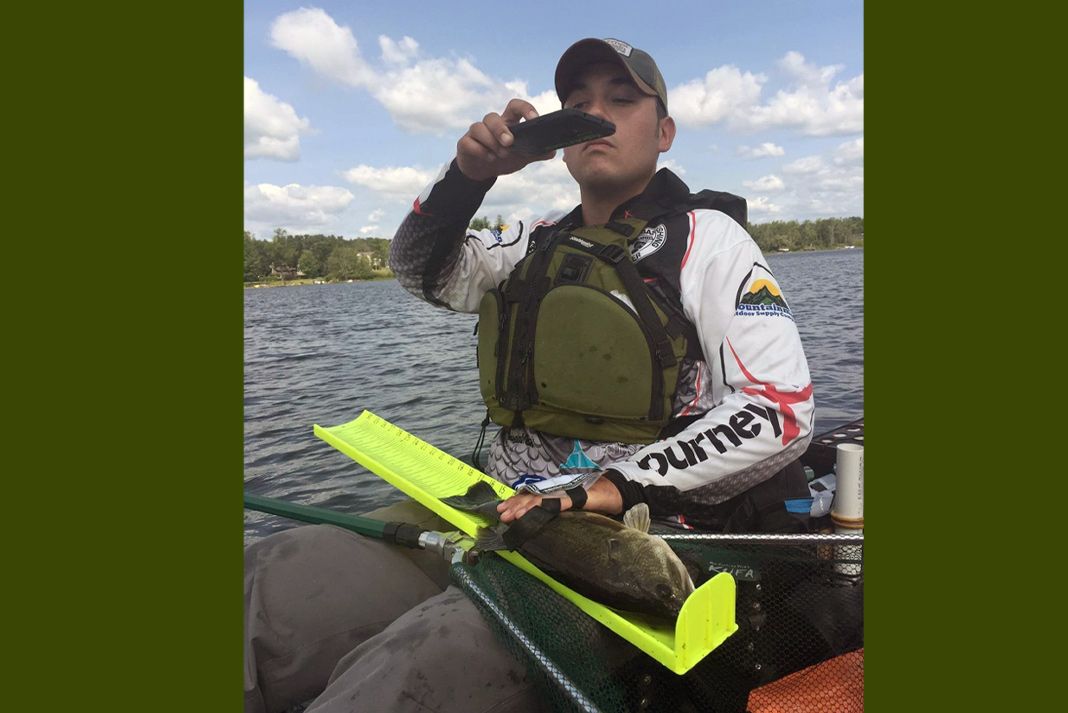 Man sitting on kayak taking a photo of fishing on his lap