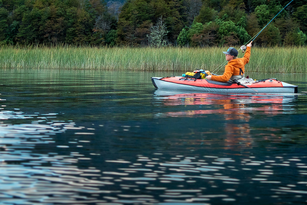 Angler casting from an inflatable fishing kayak