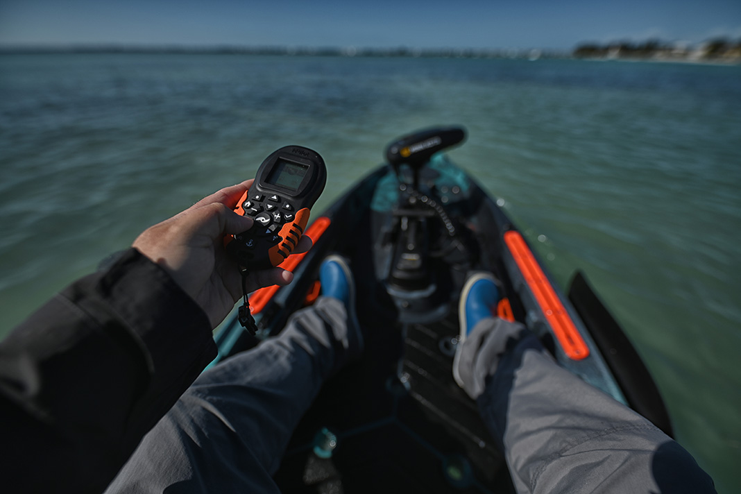 POV shot from fishing kayak. Hand holding remote control.