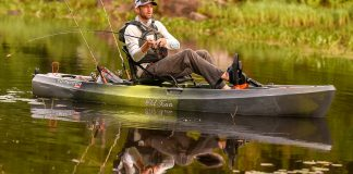 Man sitting on sit-on-top pedal drive fishing kayak, holding a rod